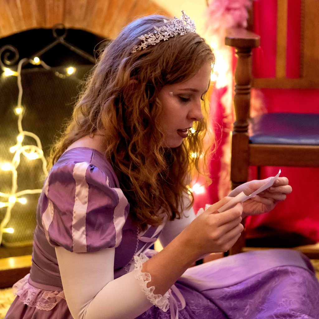 Laura dressed as a princess, reading a slip of paper